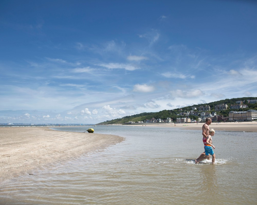 Trouville en Normandie, des vacanciers remontent vers la plage.
