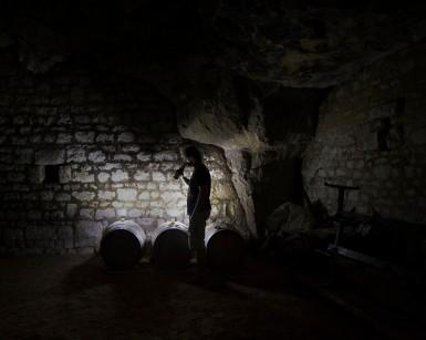 Pres de Saumur dans la Loire, vincent sent le vin au cours de son processus de fermentation alcoolique devant quelques tonneaux a la lumière de de ses lampes de poches. Cave troglodyte.