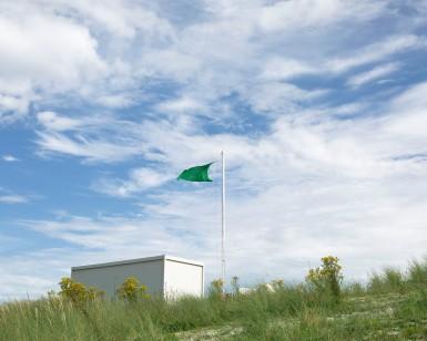 Le drapeau vert, signe de baignade sans danger, flotte a la cime de la cabine de surveillance, larmor Plage, golfe du morbihan, Bretagne