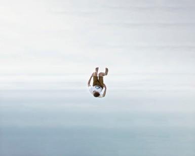 Jeune photographie sur la plage de Larmor Plage dans le golfe du Morbihan, au moment le plus d'un saut effectue grave a un ballon rebondissant a moitie en fonce dans le sable. Ce jeu permet d'effectuer diverses figures accrobatiques. Ici le jeune semble tomber du ciel